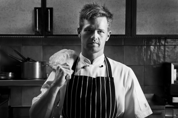 portrait of male chef with leg of lamb slung over shoulder